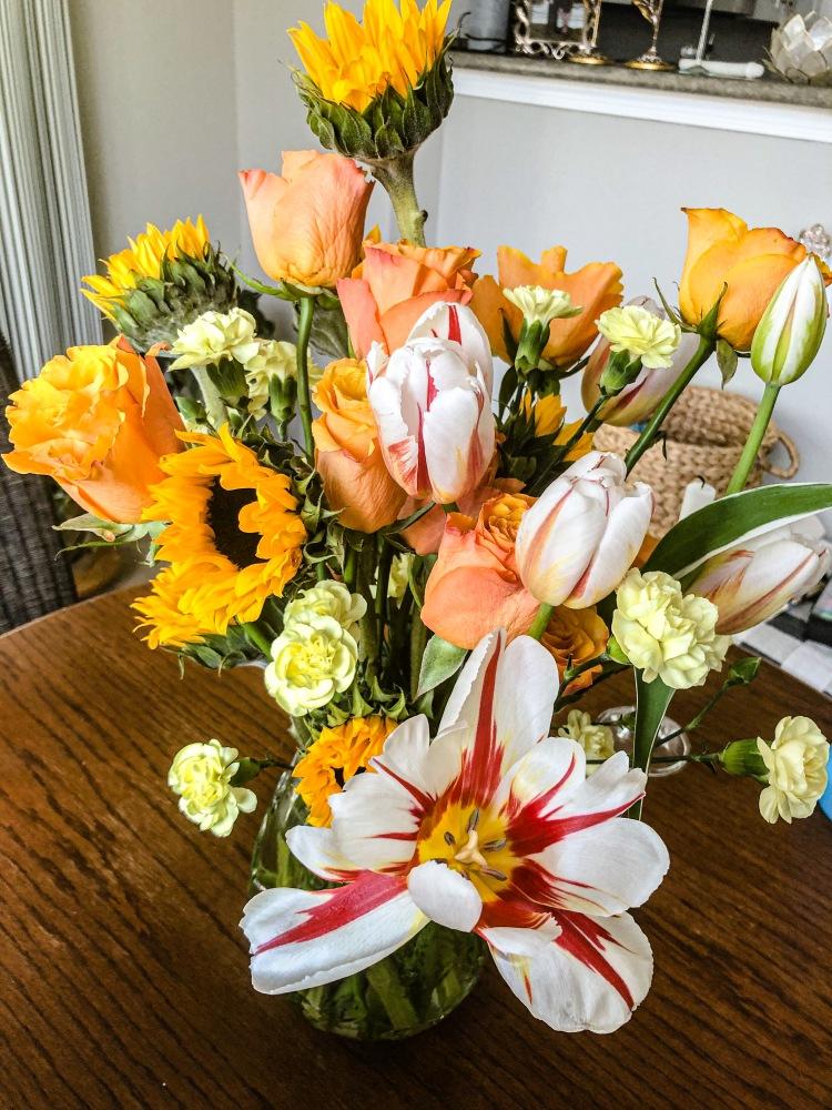 Warm floral arrangement, sunflower, tulips, orange roses, flower centerpiece